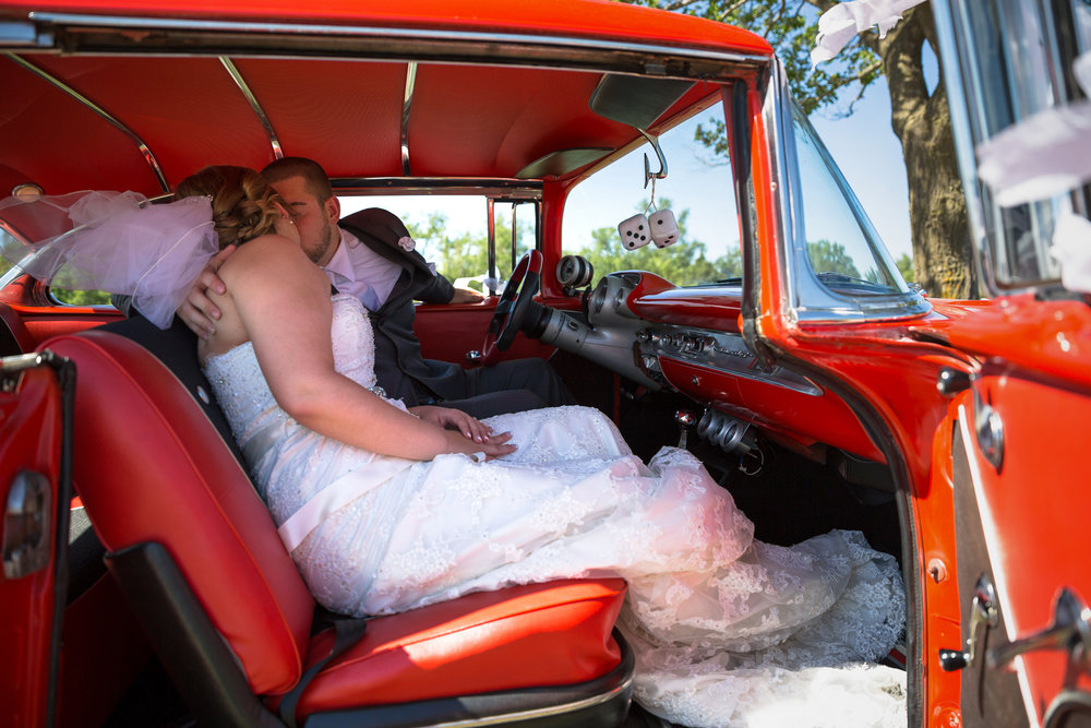 Danielle & Chris in red car - Vow Media Group Chicago Wedding Photographers