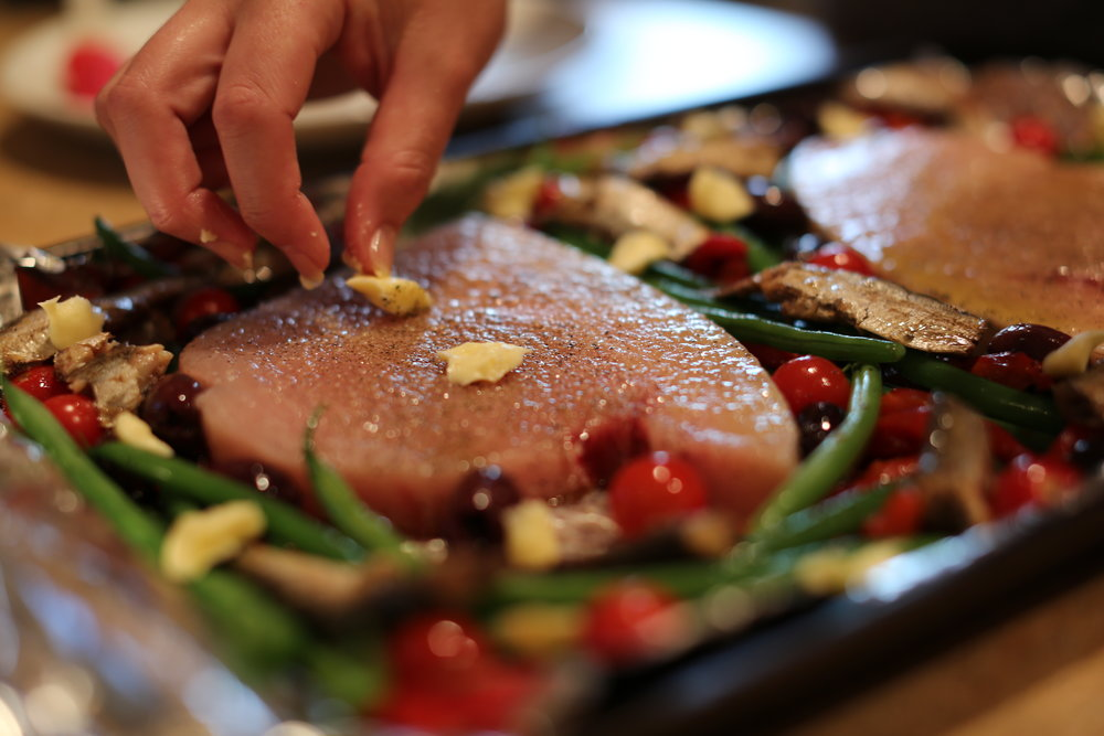 4.Brush both sides of swordfish with olive oil, salt and pepper and place on baking sheet. Dot fish and vegetable with butter.
