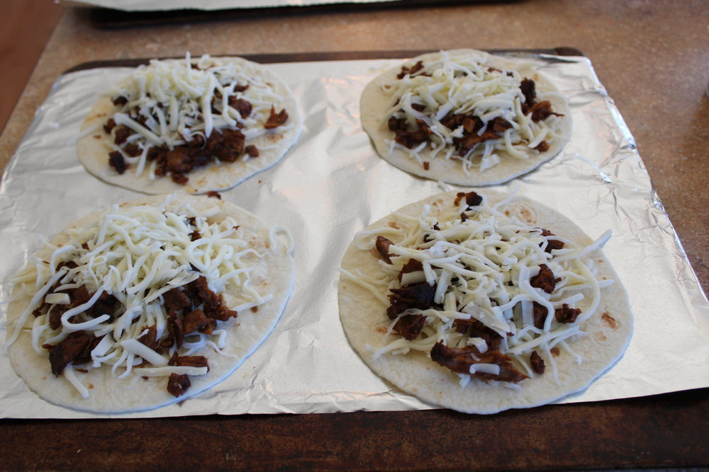 3. Prepare sheet pan by covering with aluminum foil and nonstick cooking spray.  Place tortilla, cheese, and brisket on tortilla.