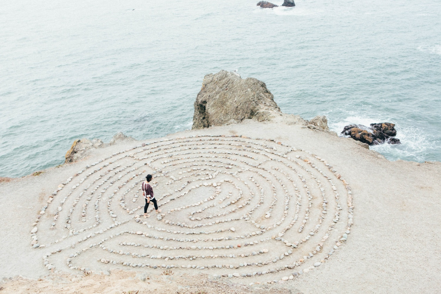 A woman walking through a maze of rocks next to the ocean.