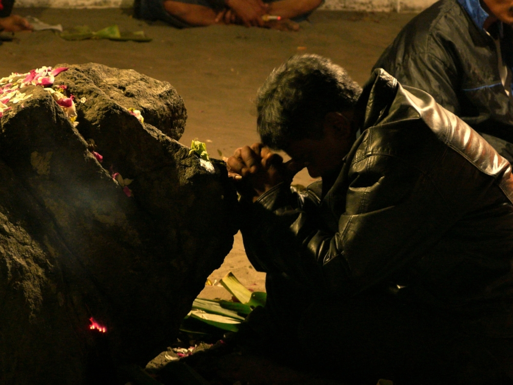 A man prays at one of Parangkusumo's sacred rocks. (Photo taken by the author.)