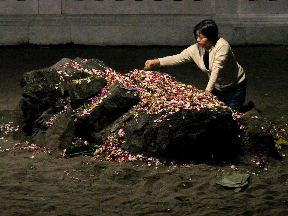 A woman sifts through flowers at one of Parangkusumo's sacred rocks. (Photo taken by the author.)