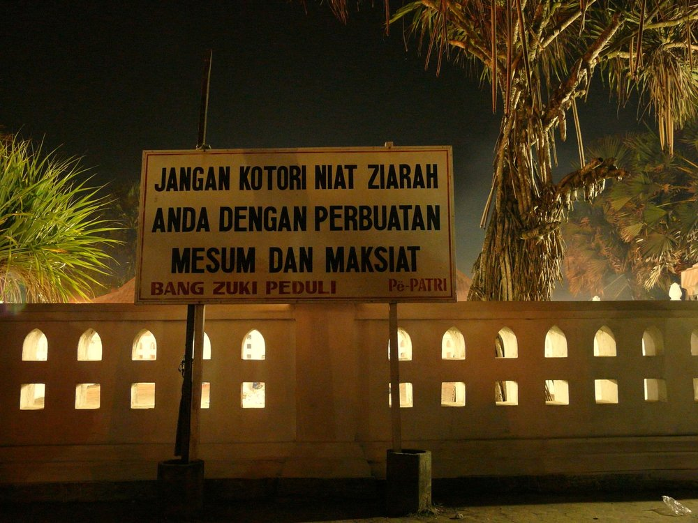 "A sign next to the sacred rocks warns visitors: ""Don't corrupt your intention to do ziarah by committing foul, sinful actions."" (Photo taken by the author.)"