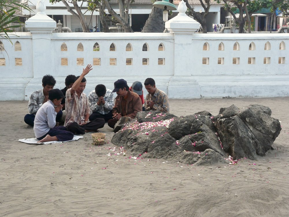 A group of visitors prays over the sacred rocks at Parangkusumo. (Photo taken by the author.)