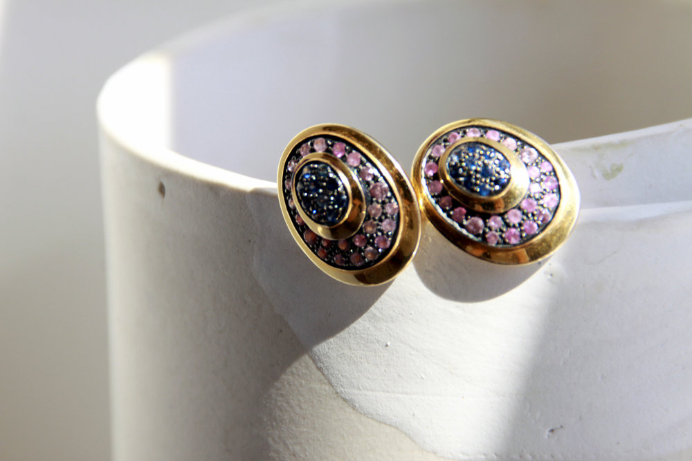 Peacock studs adorned with multi sapphires hand set in gold and black rhodium.