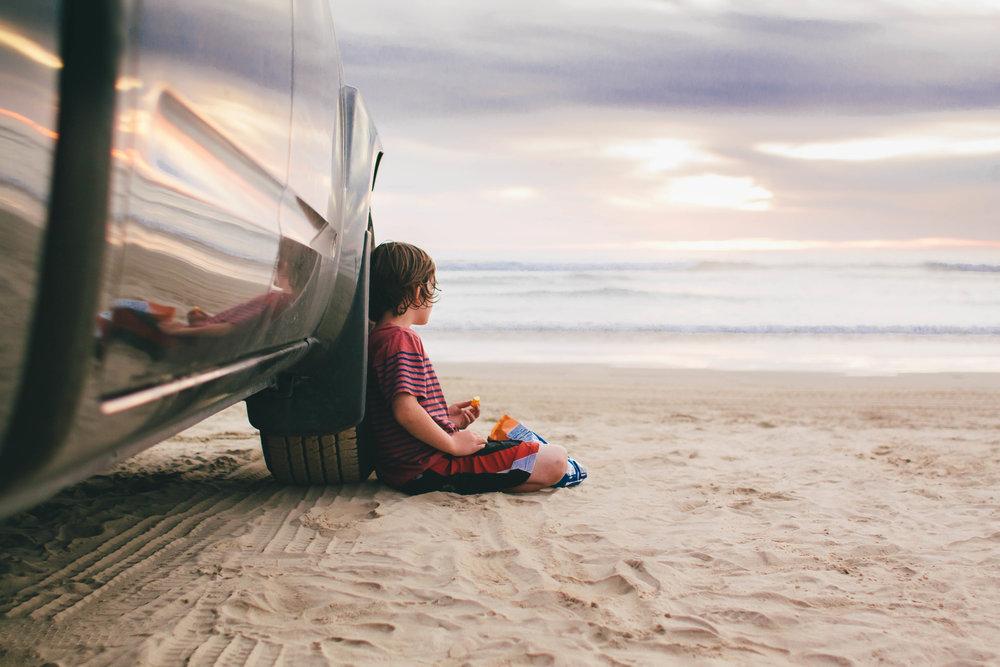 kid-sitting-next-to-car-beautiful-california-beach-sunset