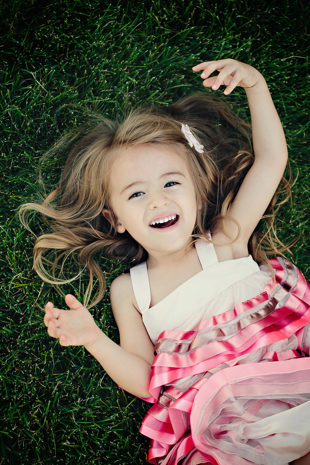 little-girl-pink-dress-laying-on-grass