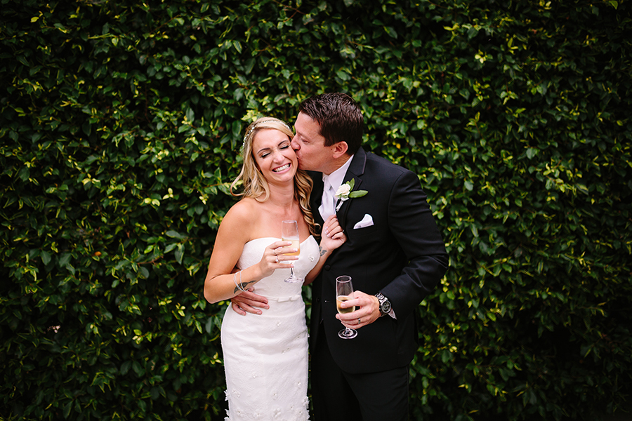 groom-kissing-bride-in-front-of-green-ivy-wall