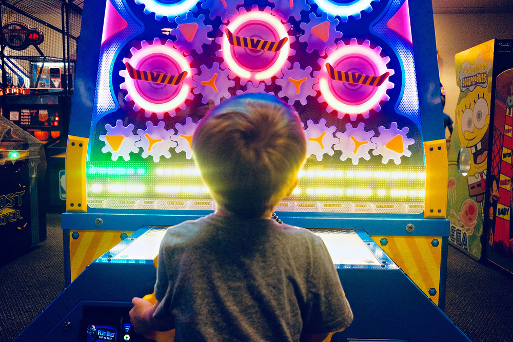 boy-playing-neon-pink-green-blue-arcade-game-silhouette