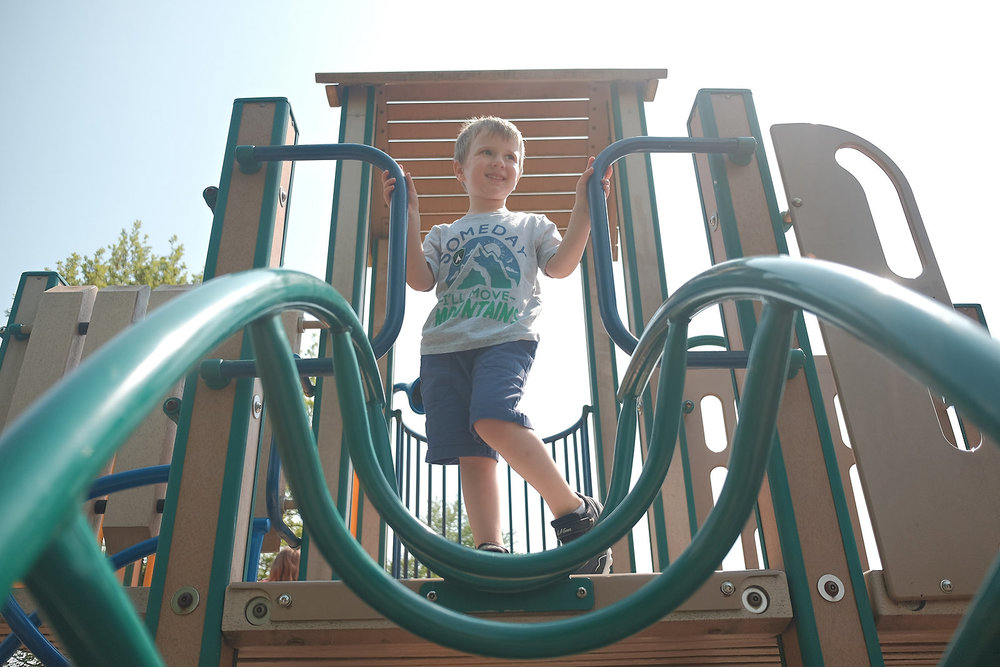 boy-standing-on-top-of-green-tan-park-playground