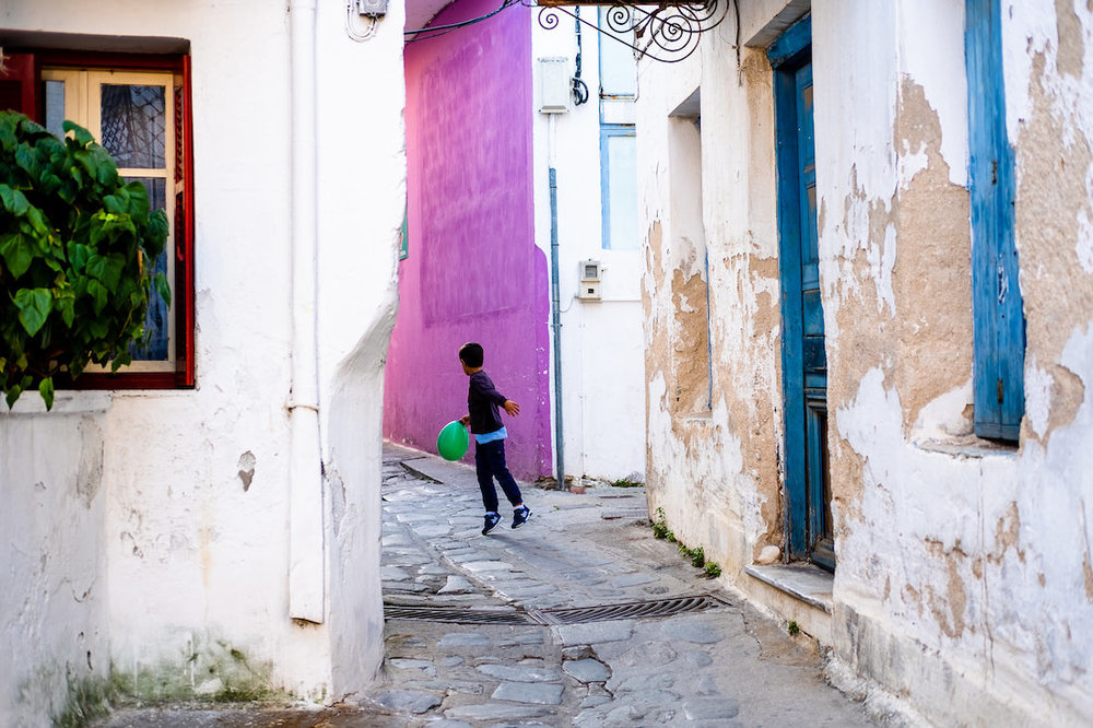 kid playing ball in streets with pink wall