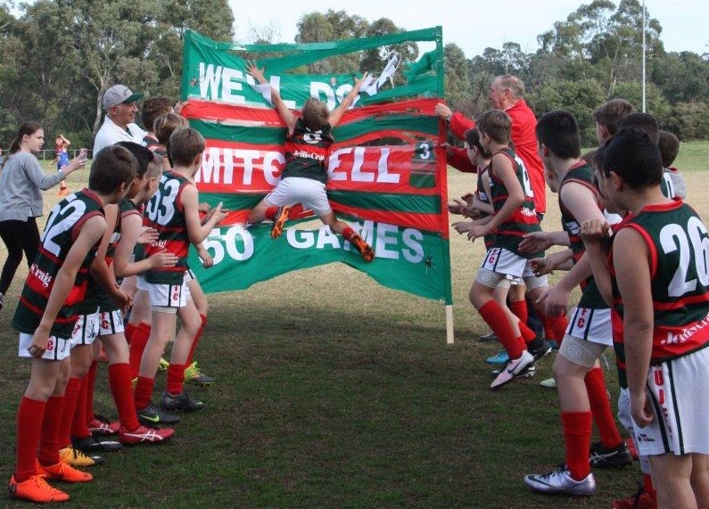 Mitchell Hall celebrates his 50th game with a splash into the banner!