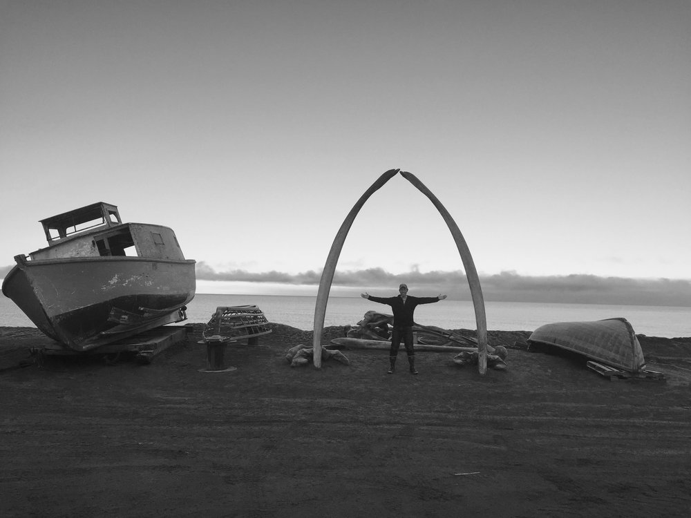 Christian stands beneath the whale bone arch, near several retired wooden boats on the beach of Barrow, Alaska.