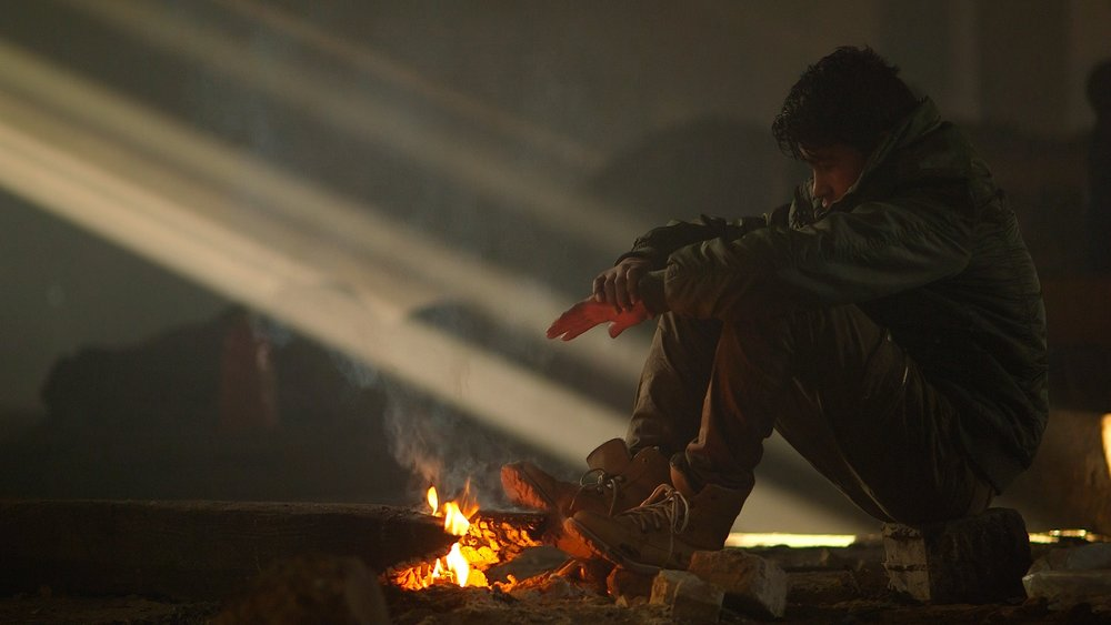 A boy sits by a fire in the squat in Belgrade, Serbia (January 2017)