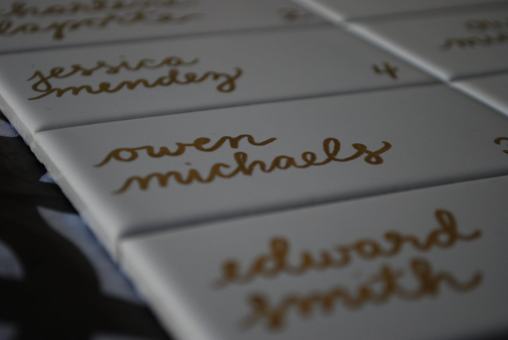 White tile escort cards with gold lettering