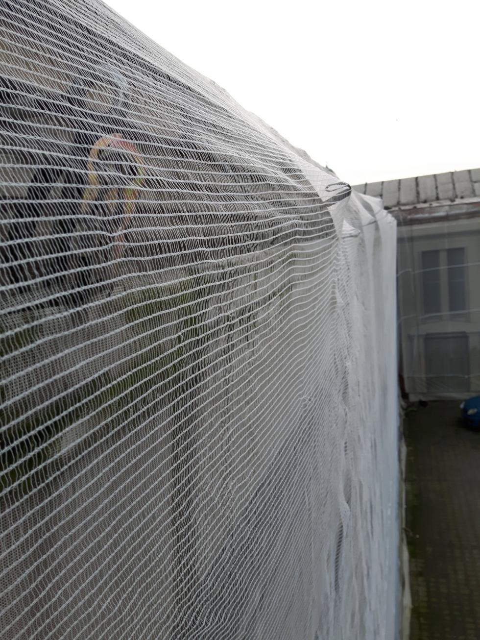 Siatka chroniąca przed odpadającymi elewmentami elewacji wykonana z polipropylenu.