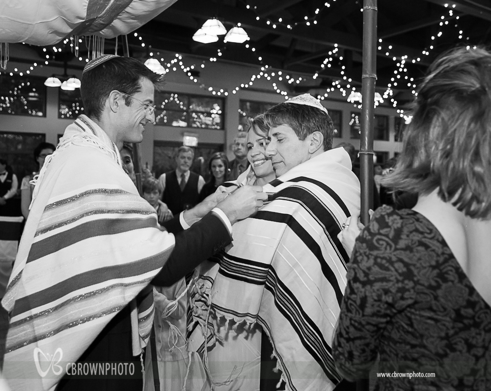 Shannon and Joel are wrapped in a prayer shawl by their rabbi.