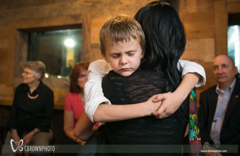 Youngster in Mom's arms near the end of wedding reception