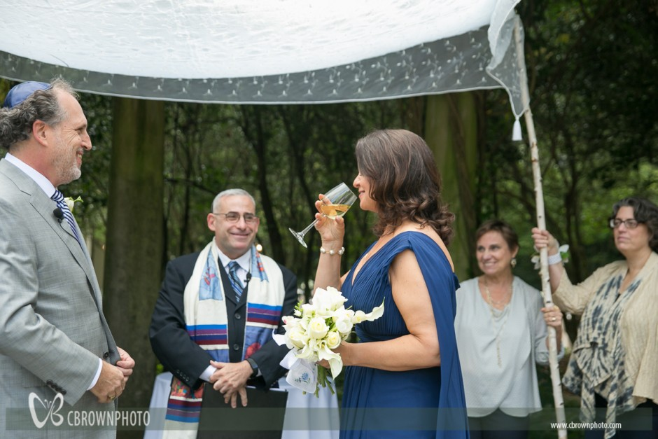 Bride and groom share wine at Jewish wedding.