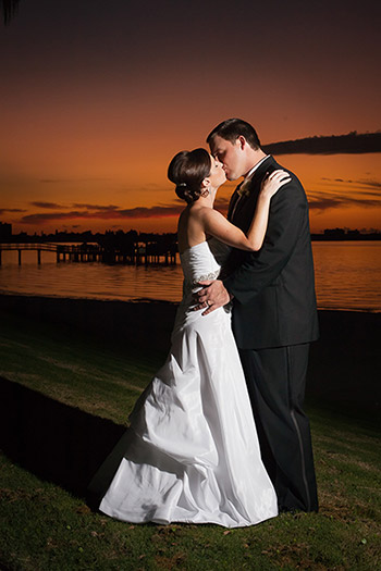 Posed photograph of bride and groom kissing at sunset by Cindy Brown.