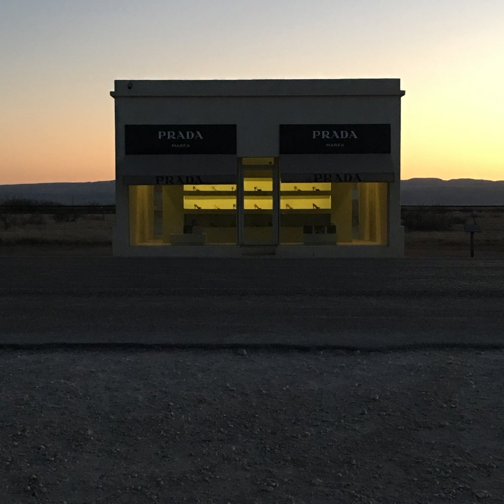 Prada Marfa with the sun setting from behind as the installation lights turn on.