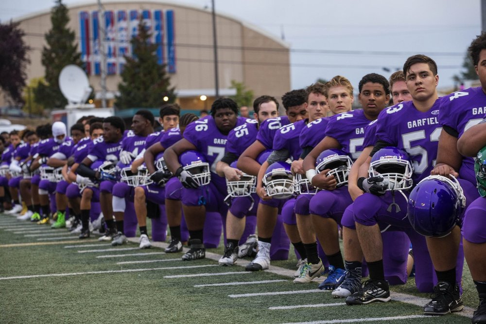 The Garfield Bulldog football team takes a knee during the national anthem Friday at the Southwest Athletic Complex. Visiting Garfield played West Seattle. (Dean Rutz/The Seattle Times) via  http://www.seattletimes.com/sports/high-school/garfield-football-team-takes-knee-prior-to-game-friday-night/