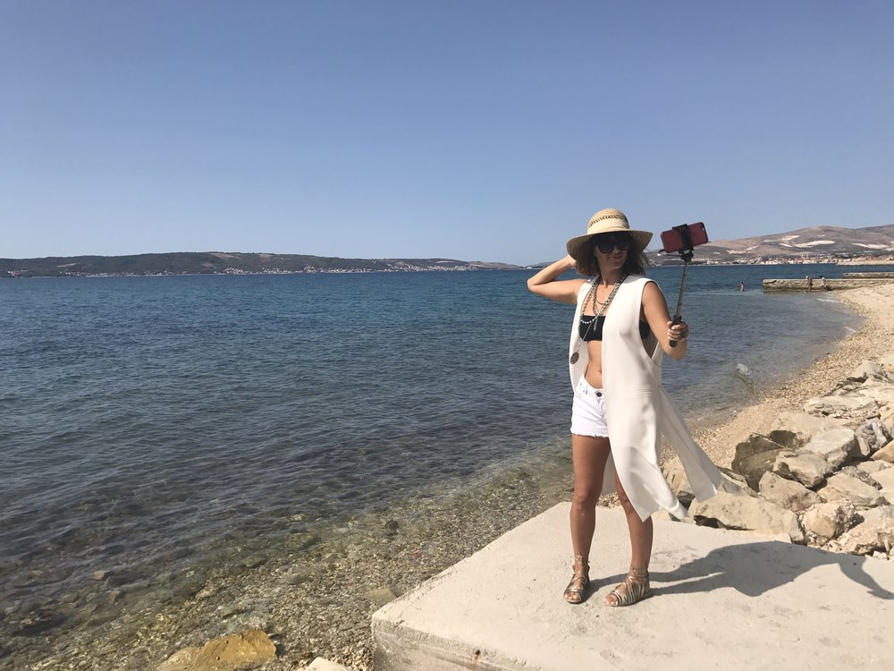 White short jeans, black bikini top and white sleeveless blazer, jewellery and golden lace up sandals, straw hat, selfie stick