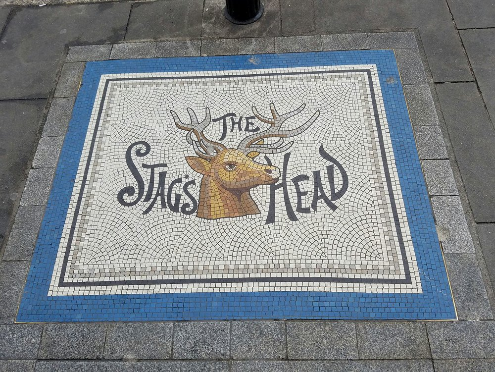 Victorian Advertising, on the sidewalk, inviting passersby to enter an alley to find The Stag's Head.