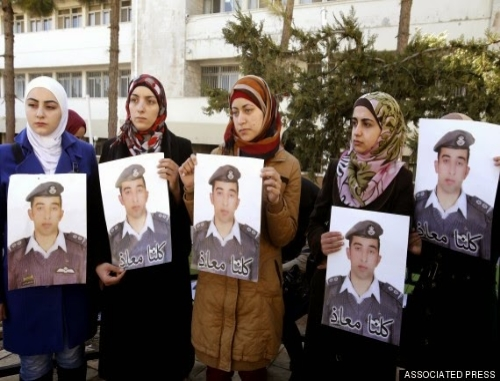Several Jordanian women with posters of Muath al-Kaseasbeh including his wife Anwar (center)