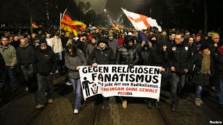 "A rally by PEGIDA, which means ""Patriotic Europeans against the Islamization of the West"""