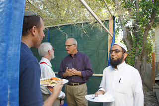 An interfaith meal and gathering in the Jewish Sukkah (courtesy  Texas Interfaith Center )