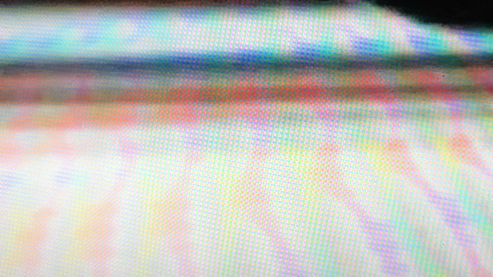Sebastian Gatz  Delirious Landscape    A video of a video of a video of the architectural structure of Pharos is creating a series of more and more abstracted patterns - made from the space for the space.  Stills of the three videos showing architectural elements which increasingly get lost in the emerging colors of the digital/analog process - conceptually playing with the notion of time, space and dimensionality (of media).  The analog tapestry and the digital image following a similar logic of order - although operating in completely different time domains. While a tapestry is constructed over months and years the digital image is provided in milliseconds.  The here described iterative process reveals the (shared) orthogonal structure in the digital image while simultaneously blurring it.  Through the tactile process of tapestry, with its analog infinite material resolution, the blurred image gets sharpened on a specific level of craft - making it work on different (spatial) scales: sharp from distance, blurred from proximity, detailed in close vicinity.  The soft emerging colors and the logic of the phenomenological dimensionality starts a dialog with James Turrell's works, which embeds the tapestry in a broader architectural / curatorial narrative.  At the same time it is a homage to the work of Nam June Paik (by referring to his media / video art works) and Jean Tinguely (and his destructive machinery).  The proposal suggests a replacement of the tapestry every year - the new based on a digital image of the old. An infinite process of digital/analog construction and destruction - playing with the irony of time in art.