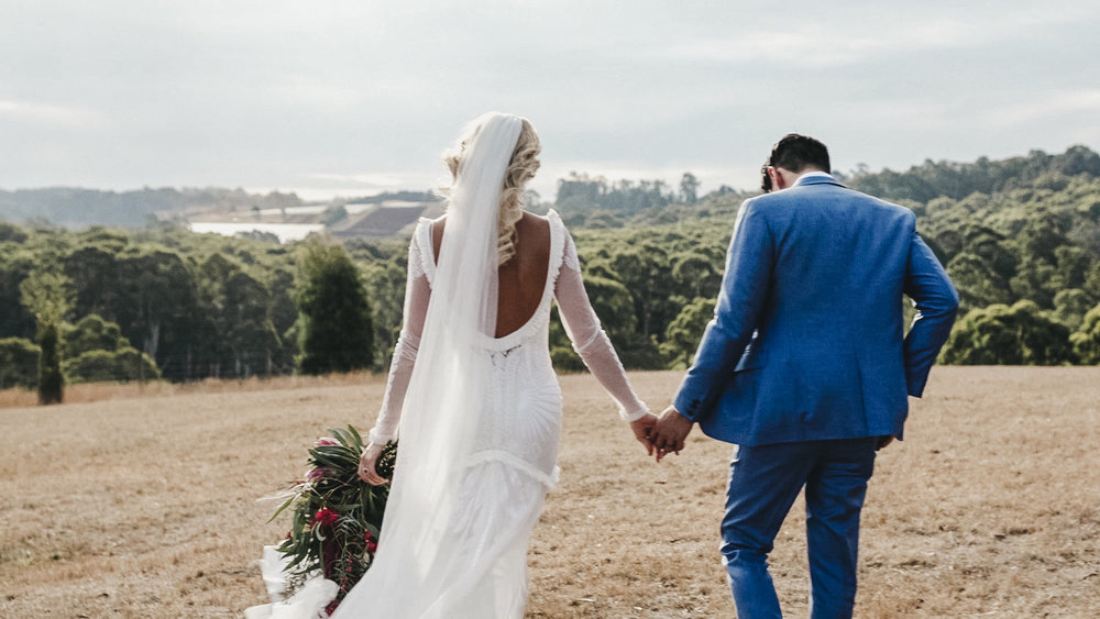 Newly married couple walking through a field in the Dandenong Ranges and Yarra Valley
