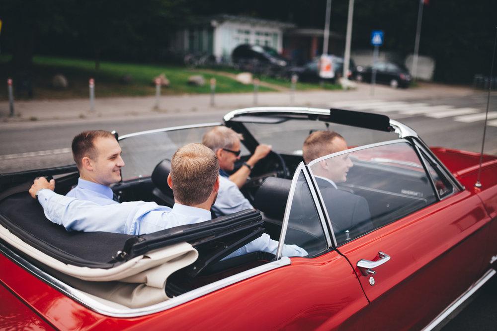 4 Männer sitzen in einem Roten Mustang in Kiel auf dem weg zu einer Hochzeit in der Seebar Düsternbrook. Das Auto fährt weg von der Kamera - die Männer schauen nach vorne. Das Foto ist von Fotograf aus Kiel Phil Schreyer im rahmen einer Hochzeitsreportage im Seebad Düsternbrook entstanden.