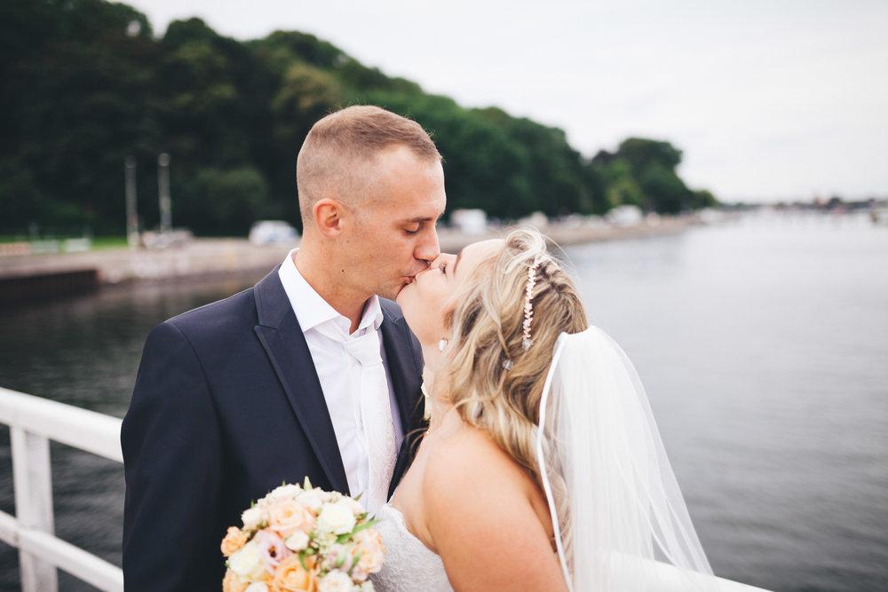 Ein Hochzeitspaar küsst sich auf einem Steg in der Seebar Kiel kurz nach der Trauung. Die Hochzeit wurde Fotografiert von Phil Schreyer.