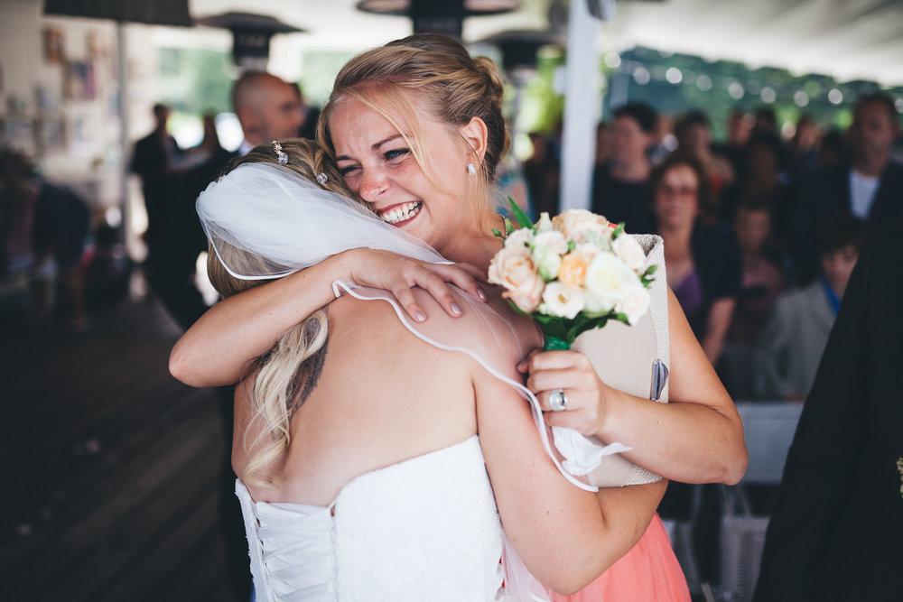 Eine junge attraktive Frau umarmt die Braut in der Seebar Kiel auf einer Hochzeit. Fotografiert von Fotograf Phil Schreyer in Kiel 2016.