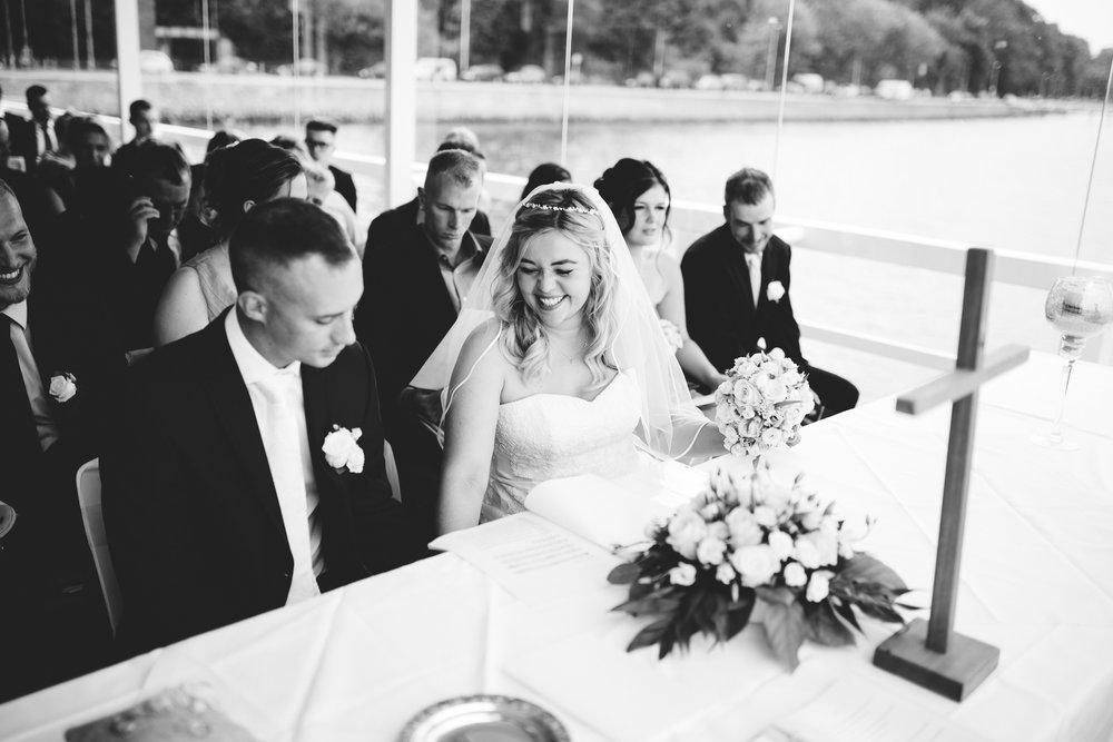 Ein Hochzeitspaar bei der Trauung in der Seebar Kiel lacht und hält sich dabei die Hände. Die Momentaufnahme stammt von Hochzeitsfotograf Kiel Phil Schreyer