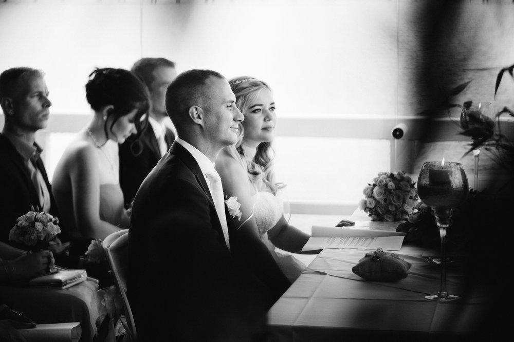 Eine S/W Aufnahme von einem Hochzeitspaar in der Seebar Kiel. Sie sitzen bei der Trauung am Tisch und schauen zum Trauredner. Die Momentaufnahme stammt von Fotograf Kiel Phil Schreyer