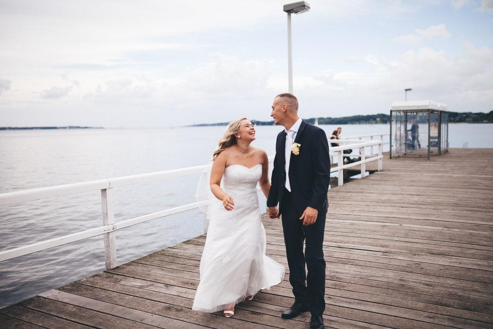 Ein Hochzeitspaar läuft über das Steg der Seebar Kiel und schaut sich dabei lachend an. Sie sind frisch verheiratet und Glücklich. Fotografier im rahmen einer Hochzeit von Phil Schreyer 2016