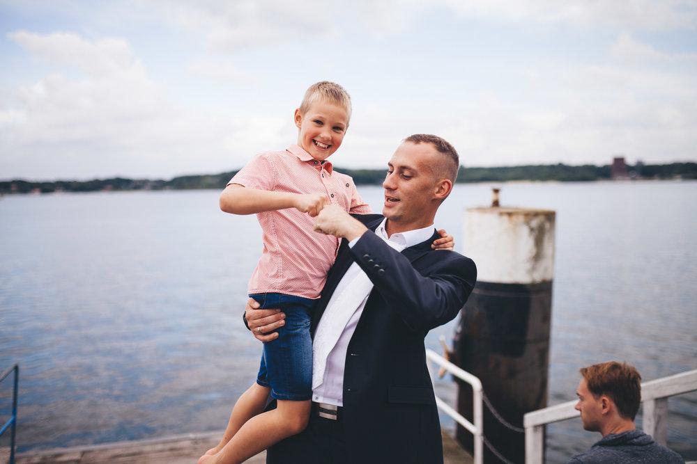 """Ein Mann gibt seinem Sohn ein """"High Five"""" bei einer Hochzeit an der Förde. Der junge grinst und der Vater lacht ebenfalls. Der junge hat ein rotes Hemd an, der Mann einen Anzug."""