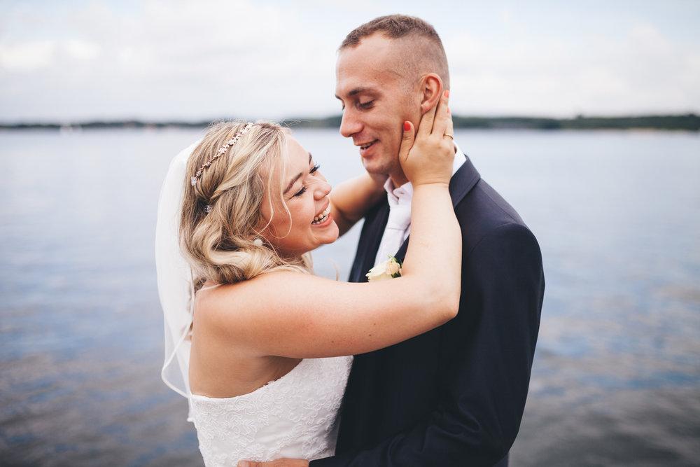 Eine Frau hält ihren mann hinterm kopf fest und lacht dabei. Sie sind verliebt und frisch verheiratet. Fotografiert bei einem Fotoshooting in Kiel von Phil Schreyer