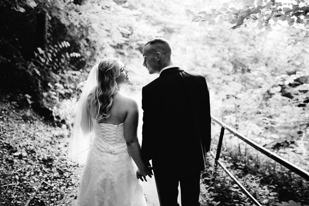 Ein Hochzeitspaar läuft über einen Wald weg. Sie halten Händchen und schauen sich an. Das Foto ist Schwarz Weiß. Die Aufnahme entstand bei eine Fotoshooting in Kiel