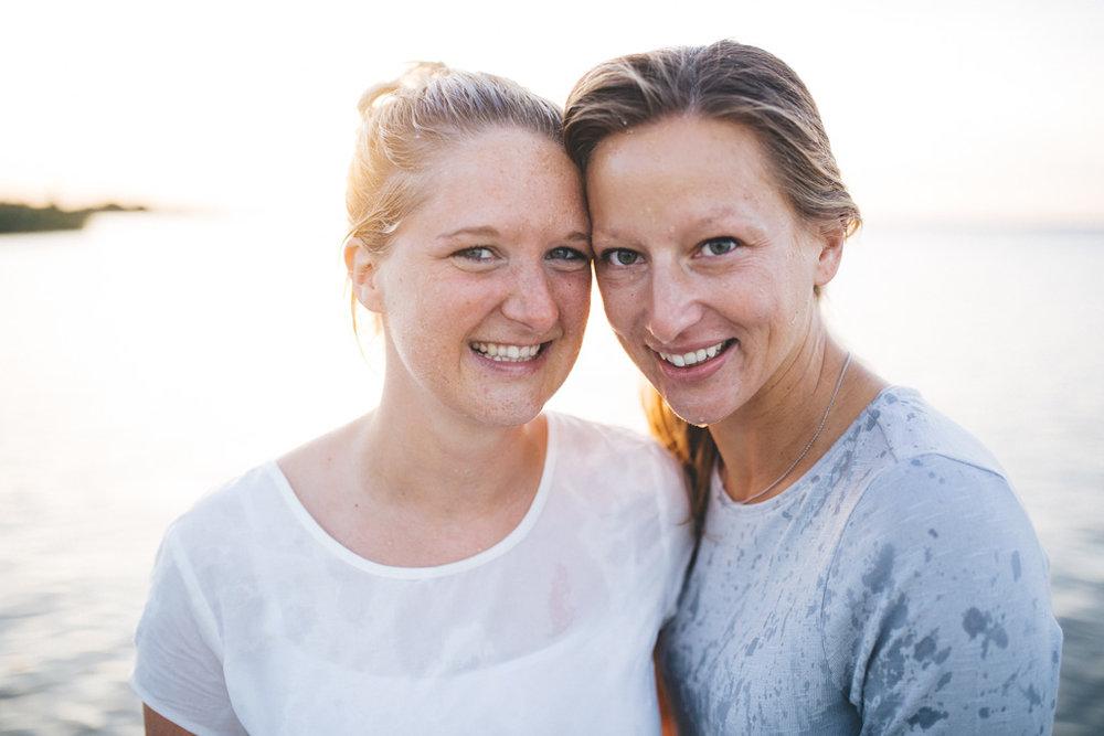 zwei Faruen lachen sich an. Sie stehen im Wasser und sind Nass. im Hintergrund geht die Sonne unter. Fotoshooting Kiel.