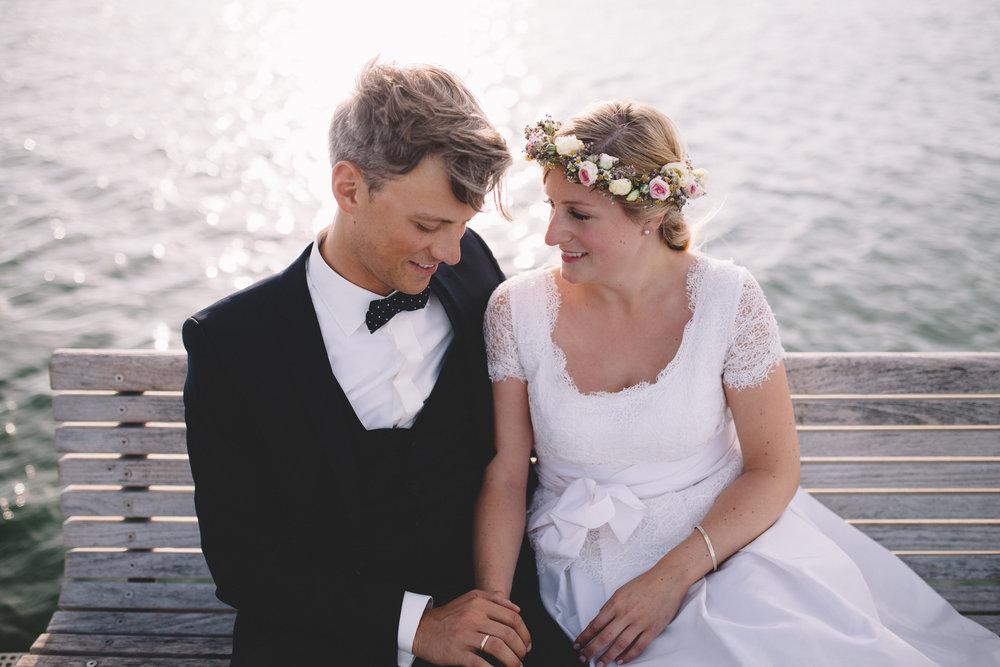 Hochzeitspaar sitzt auf einer Bank am Wasser und schaut sich an. Beide lachen und die Braut hat einen Blumenkranz im Haar. Das Foto wurde von Fotograf Phil Schreyer geschossen