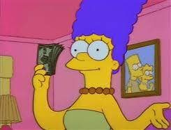 Image description: Marge Simpson holds a wad of cash.