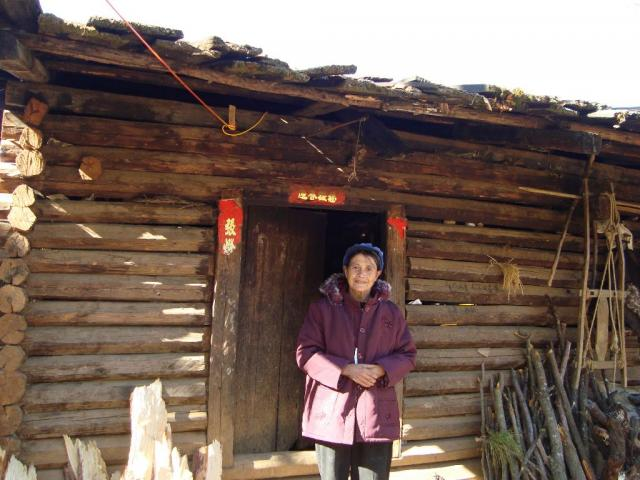 Lisu women outside her home wearing new winter coat