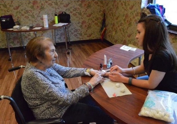 Ellen giving a senior a manicure at a GlamourGals makeover.