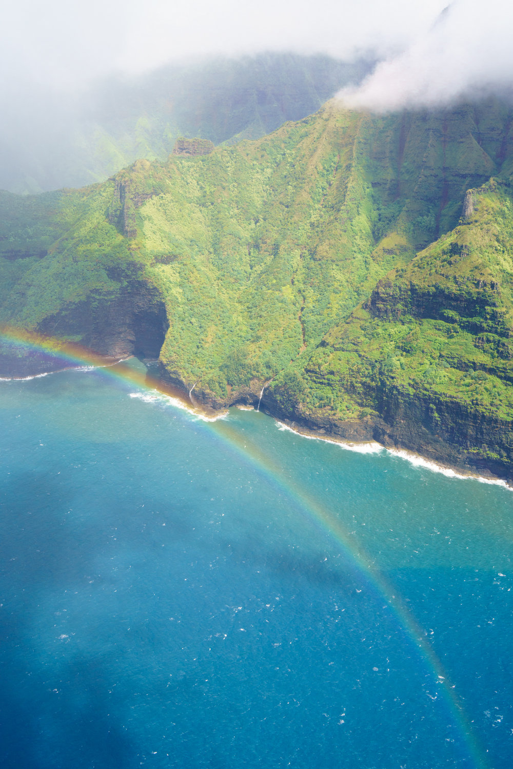 Rainbows and waterfall views along the Na Pali Coast Kauai | Never Settle Travel