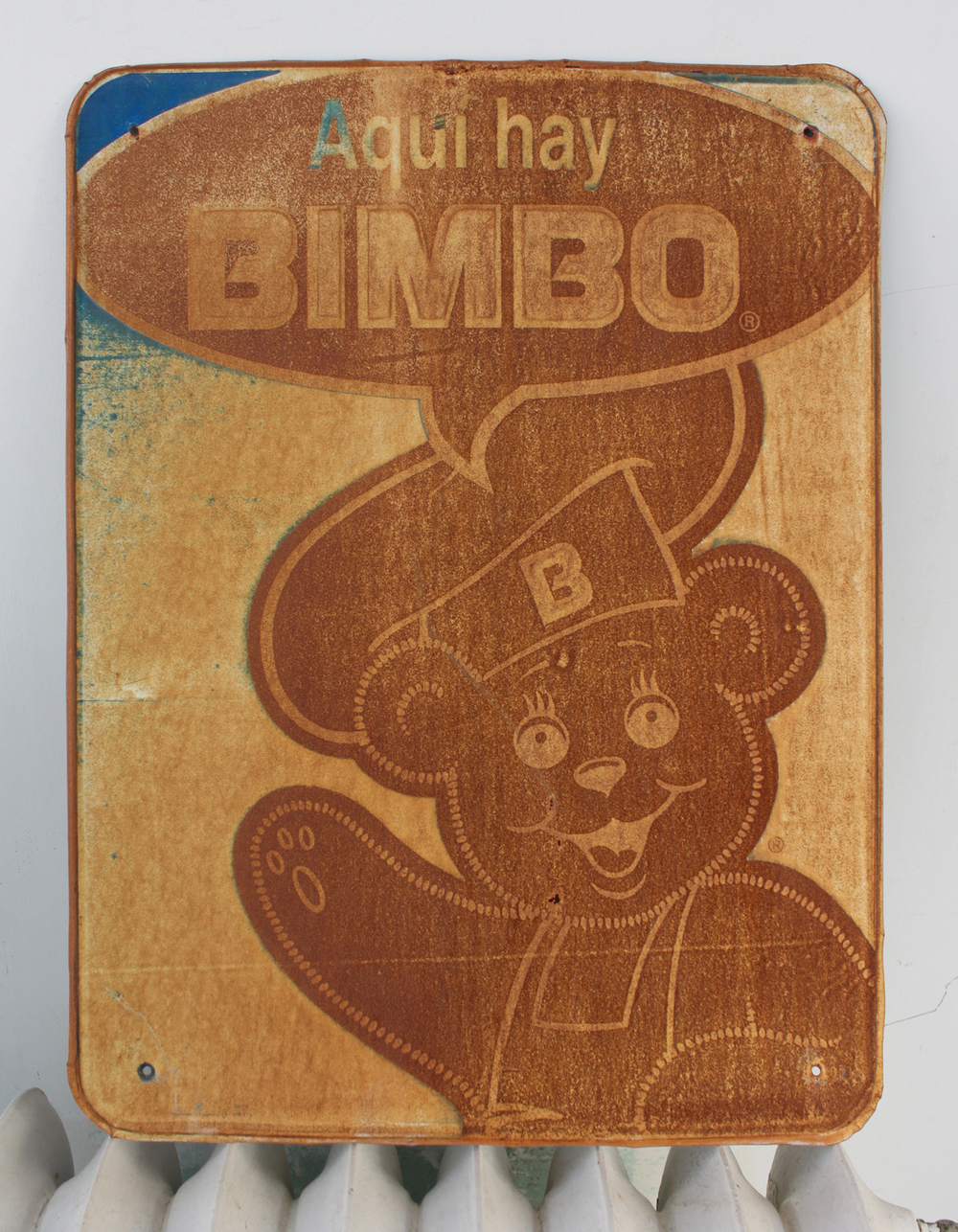 "What makes this sign in my collection so fun is the talk bubble with the word BIMBO which is actually the name of a Mexican loaf of bread but we all know what it means in English. Translated it says ""Get your Bimbo here."" I also like the way that the image has become a negative of itself as the sun burned out the color and the rust took over. The touch of blue, the white space, the line work all makes for a nicely done design. Found it on the side of an old Mexican neighborhood corner store not far from the mountainside near Scenic Drive. I bought it from the store clerk who first asked the BIMBO salespeople if he could get a new sign because the old sign had seen better days. He got his new sign and I got the priceless one."