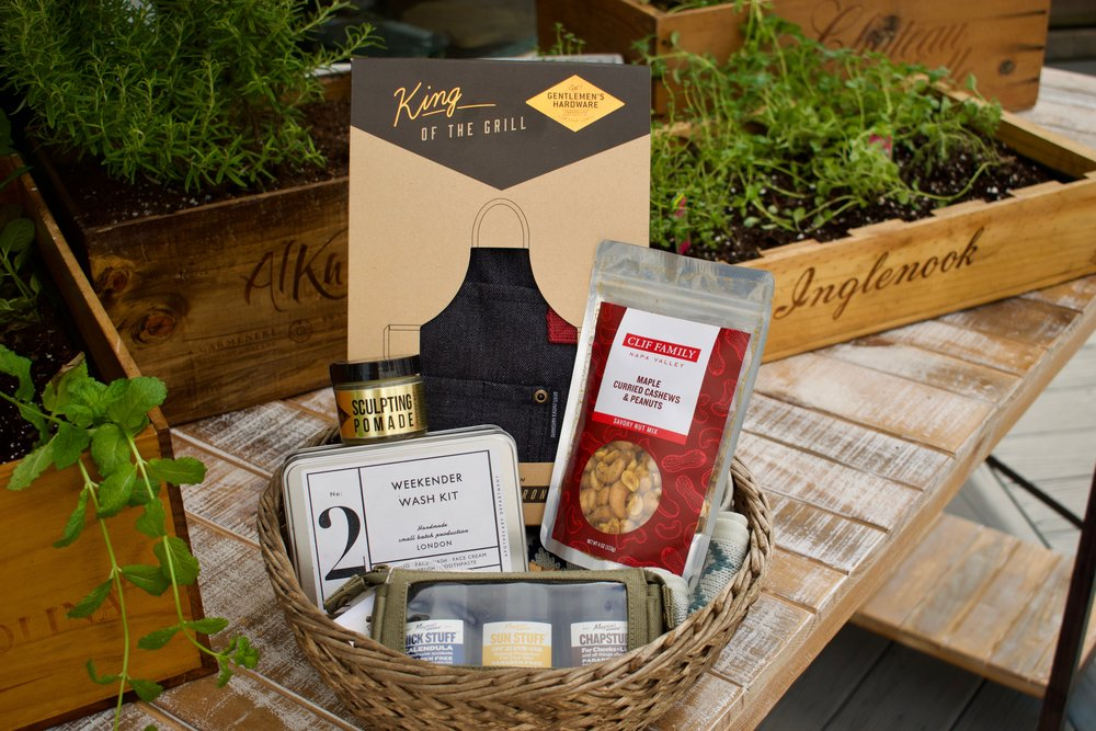 1. King of the Grill Chef's Apron, Weekender Wash Kit – travel size shampoo, body & face wash, face cream, and toothbrush & toothpaste. Maple Curried Cashews & Peanuts, Stuff Road Pack – post razor balm, sunscreen face stick, chapstick. Men's Grooming Set -- sculpting pomade, aftershave, clary sage & vetiver beard